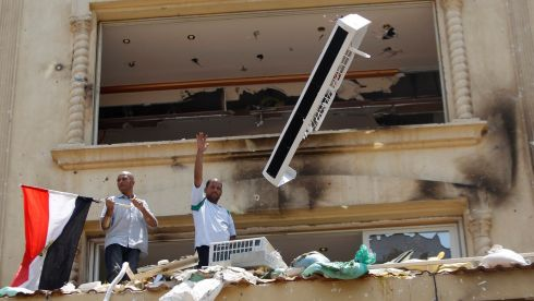 A looter gestures as part of an air-conditioning is thrown down from the Muslim Brotherhood's headquarters. Photograph: Amr Abdallah Dals/Reuters