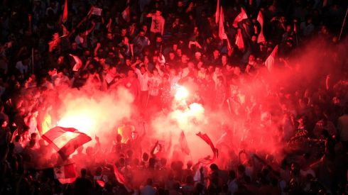 Protesters gather near a lit flare during a protest at Tahrir Square in Cairo. Photograph: Mohamed Abd El Ghany/Reuters