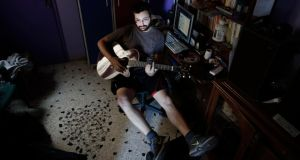 Geography student George Boukouvalas, 23, who lost his job at a warehouse 14 months ago and has been unable to find work since, plays the guitar in his home at Peristeri suburb in Athens.