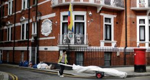 A man  wheels a trolley past the Ecuadorian Embassy in London, England. Ecudaor has claimed today that a secretmicrophone was found in the building, where Wikileaks founder  Julian Assange has lived for a year. Photograph:  Matthew Lloyd/Getty Images.
