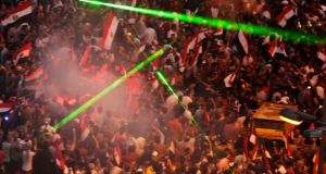 Laser lights are flashed as protesters against Egyptian President Mohamed Mórsi gather in Tahrir Square in Cairo this evening. Photograph: Asmaa Waguih/Reuters