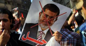 "An anti-president Mohammed Morsi poster is viewed as as thousands of Egyptians demonstrate against him in Tahrir Square on Wednesday. ""While Morsi gained considerable popularity by sending the military back to barracks, he lost the confidence of many Egyptians when, last November, he issued a decree giving himself powers beyond judicial review"". Photograph: Spencer Platt/Getty Images"