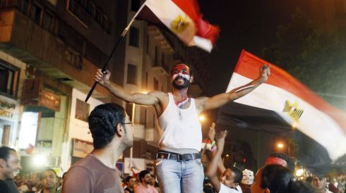 An anti-Morsi protester dances as people celebrate near Tahrir square after the announcement of the removal from office of Egypt's deposed president. Photograph:  Asmaa Waguih/Reuters