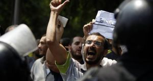 Members of the Muslim Brotherhood and supporters of ousted Egyptian president Mohamed Morsi shout slogans in front of riot police and Egypt's Constitutional Court during the swearing in ceremony today of the head of the court Adli Mansour as the nation's interim president. Photograph: Amr Abdallah Dalsh/Reuters