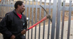 A man forces open the gate of the property of Mandla Mandela, grandson Nelson Mandela, following a court hearing clearing the way to remove the remains of the former leader's children from his property . Photograph: Siegfried Modola /Reuters