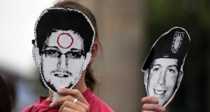 "People hold portraits of former US spy agency contractor Edward Snowden (left) and US Army Private  Bradley Manning, a suspected whistleblower who is on trial in the US for ""aiding the enemy"",  during a protest in front the Brandenburg Gate in Berlin. Photograph: Thomas Peter/Reuters"
