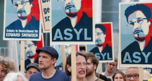 Demonstrators in Germany hold placards urging that Edward Snowden be offered asylum. Photograph: Reuters