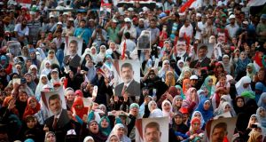 Protesters carry posters of ousted Egyptian president Mohammed Morsi during a rally in the Nasr City neighborhood of Cairo. Photograph: Tara Todras-Whitehill/the New York Times
