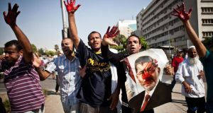 Islamist protesters, one with a picture of ousted president Mohamed Morsi, show bloodied hands after troops opened fire in Nasr city, Cairo. Photograph: AP