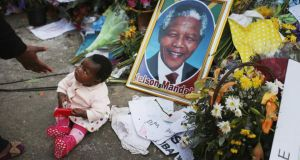 A little girl has her photograph taken as she and her family pay tribute to Nelson Mandela at the memorial wall near the Medi-Clinic Heart Hospital. Photograph: Christopher Furlong/Getty Images