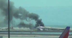Smoke rises from plane at San Francisco Airport in this screengrab from unverified YouTube clip.