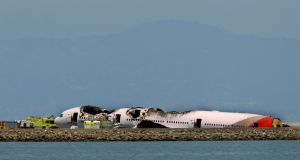 The San Francisco skyline is seen in the background as an Asiana Airlines Boeing 777 plane lies off the runway after it crashed while landing at San Francisco International Airport. Photograph: Jed Jacobsohn /Reuters