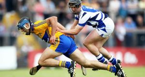 Clare's Brendan Bugler under pressure from James Walsh of Laois at Cusack Park on Saturday. Photo: Ryan Byrne/Inpho