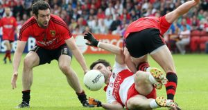 Derry's Eoin Bradley fights for possession with Down's Kevin McKernan and Ryan Boyle. Photograph: Inpho