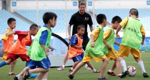 David Beckham plays soccer with children at Nanjing Olympic Sports Centre last month. Beckham is so popular in China that about 1,000 fans stampeded when he arrived to visit Shanghai Tongji University, resulting in seven people being injured. Photograph: Lintao Zhang/Getty Images
