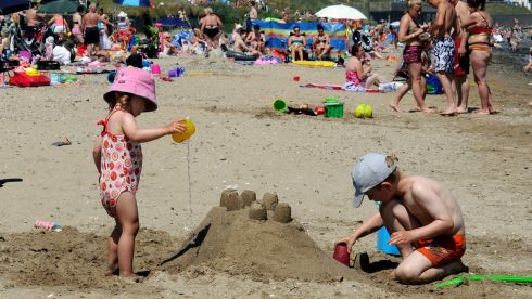 Siblings Leah Jakubowska (2) and Ethan Jakubowski (6) get their priorities right, playing in the sunshine at Portmarnock strand.  Photograph: Dave Meehan