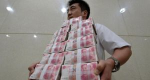 An employee carries bundles of 100 yuan notes in a bank in Shainxi province. Photograph: Jon Woo/Reuters