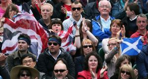Fans waving a Union flag and the Scottish national flag cheer Andy Murray during this year's Wimbledon tennis championships. Photograph: Clive Brunskill/Getty Images