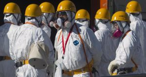 The 9.0 magnitude strong earthquake struck offshore on March 11th at 2:46pm local time, triggering a tsunami wave of up to ten metres which engulfed large parts of north-eastern Japan, and also damaging the Fukushima nuclear plant and threatening a nuclear catastrophe.  Workers wearing protective suits and masks work at the crippled Fukushima Daiichi nuclear power plant in Fukushima prefecture in November, 2011.  Photograph: David Guttenfelder/Pool/Reuters