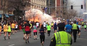 Runners continue to run towards the finish line of the Boston Marathon as an explosion erupts near the finish line of the race. Photograph: Dan Lampariello/Reuters