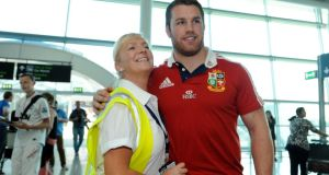 Returning Lion Seán O'Brien with a staff member at Terminal Two in Dublin airport on his arrival  from Australia. Photograph: Dave Meehan