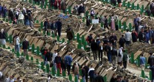 Relatives of 8,000 Muslim men and boys slaughtered in the 1995 Srebrenica massacre walk between rows of coffins next to freshly-dug graves, looking for those belonging to their relatives  in March  2003. Photograph: Danilo Krstanovic/Reuters