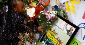 A child places flowers outside the hospital where ailing former president Nelson Mandela is being treated in Pretoria today. Photograph: Mike Hutchings/Reuters