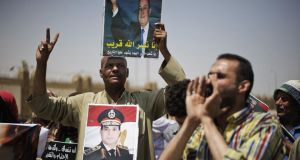 An Egyptian man holds pictures of former president Hosni Mubarak (top) and military chief Gen Abdel Fattah al-Sisi (centre). Despite Mubarak's ousting in 2011, Gen al-Sisi – a faloul – retains a prominent role in the country's power structure as military chief and defence minister. Photograph: Gianluigi Guercia//AFP/Getty Images