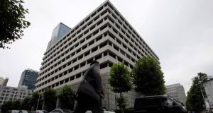 A man walks past the Bank of Japan headquarters in Tokyo. The bank said an economic recovery was underway as it kept monetary policy steady today.  Photograph: Toru Hanai/Reuters.