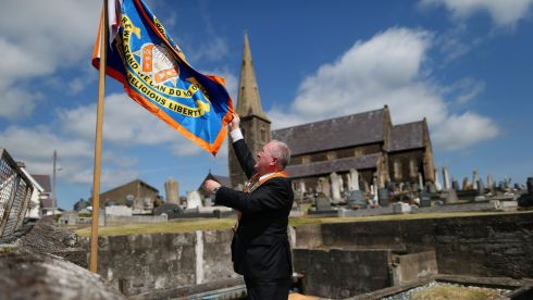 An Orange Order member erects a flag  outside Drumcree Church in Portadown, Co Armagh, during the annual Orange Order parade to the church. Photograph: Julien Behal/PA Wire