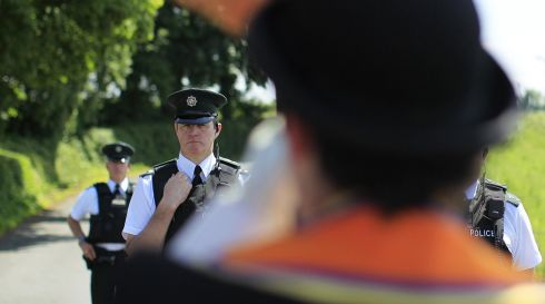 PSNI officers in front of Orange Lodge members as they stop at the barricade below Drumcree church. Photograph: Julien Behal/PA Wire