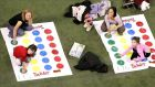 People play Twister, which remains a best-seller, 50 years after it was created.