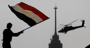 An opponent of Egypt's ousted president Mohammed Morsi waves a national flag as a military helicopter flies over Tahrir Square in Cairo. Photograph: Amr Nabil/AP