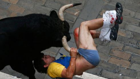Battle of man and bull: the runner is gored. Photograph: Susana Vera/Reuters