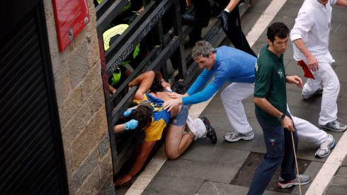 The injured runner is helped to safety. Photograph: Susana Vera/Reuters