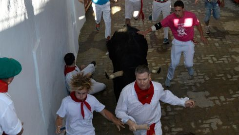 Runners sprint alongside Dolores Aguirre fighting bulls at the entrance to the bull ring during the second running of the bulls of the San Fermin festival in Pamplona. Several runners suffered light injuries in this particular run, which lasted 2m 25s, according to local media. Photograph: Vincent West/Reuters