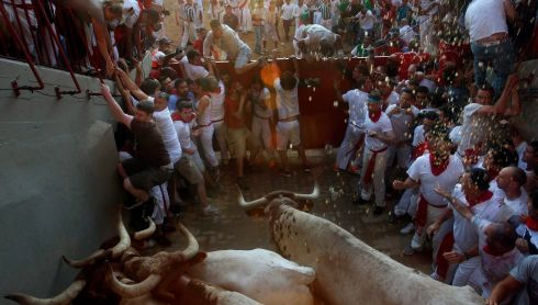Another fine mess you've gotten me into...runners trapped by steers at the entrance to the bull ring during the third running of the bulls. Photograph: Susana Vera/Reuters