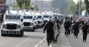 PSNI in riot gear move into position to escort the Orange Order feeder parade past the Ardoyne shops. Photograph: Paul Faith/PA Wire