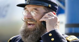 A Civil War reenactor in an officer's uniform chats on his cell phone in the Union camp during the Battle of Gettysburg reenactment . Photograph:  Melanie Stetson Freeman