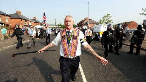 Orange Order members are flanked by riot police as they march past the nationalist Ardoyne area  in Belfast. Photograph: Cathal McNaughton/Reuters