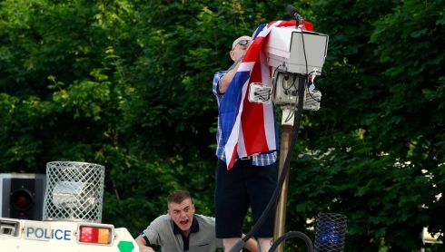 A man covers a surveillance camera with a Union Jack flag after climbing on top of an armoured police 4x4 ahead of an Orange Order parade past the nationalist Ardoyne area of the Crumlin Road in Belfast. Photograph: Cathal McNaughton/Reuters