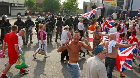 Loyalist supporters follow the parade past riot police. Photograph: Cathal McNaughton/Reuters