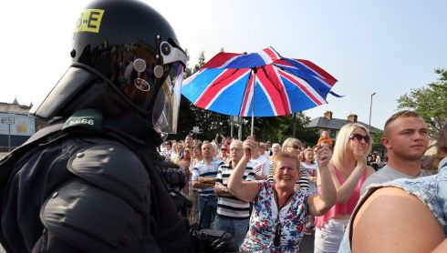 A PSNI officer in riot gear looks enormous beside the loyalist marchers. Photograph: Paul Faith/PA Wire