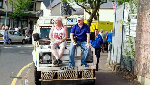Loyalists sit on an armoured police Land Rover as the Orange Order parade passes.  Photograph: Cathal McNaughton/Reuters
