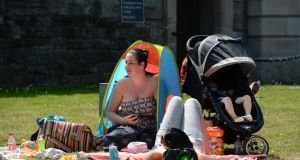 Ciara Dunphy from Ringsend taking shelter in a tent while enjoying the sunshine with friend Sutherland at Beggars Bush today. Photograph: Cyril Byrne /The Irish Times