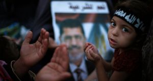 Supporters of the deposed Egyptian president Mohamed Mursi pray next to his picture during a protest in Cairo yesterday. Photograph: Suhaib Salem/Reuters