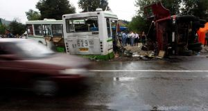 A car drives past the scene of a collision between a bus and a truck outside Moscow July 13, 2013. Seventeen people were killed and many more injured on Saturday when a truck plowed into a bus in a Moscow suburb, breaking it in two, Russia's emergency ministry said. REUTERS/Sergei Karpukhin
