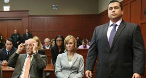 George Zimmerman stands when the jury arrives to deliver the verdict in his murder trial as his attorneys  Don West and Lorna Truett await the announcement. Photograph: Joe Burbank/Reuters.