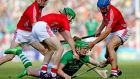 Cork's Lorcan McLoughlin, Tom Kenny and Daniel Kearney tackle Seamus Hickey of Limerick. Photograph: Inpho