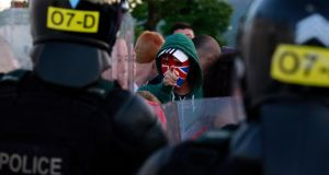 A Loyalist protester gestures to the police in the Woodvale Road area of North Belfast last night. Photograph: Cathal McNaughton/Reuters